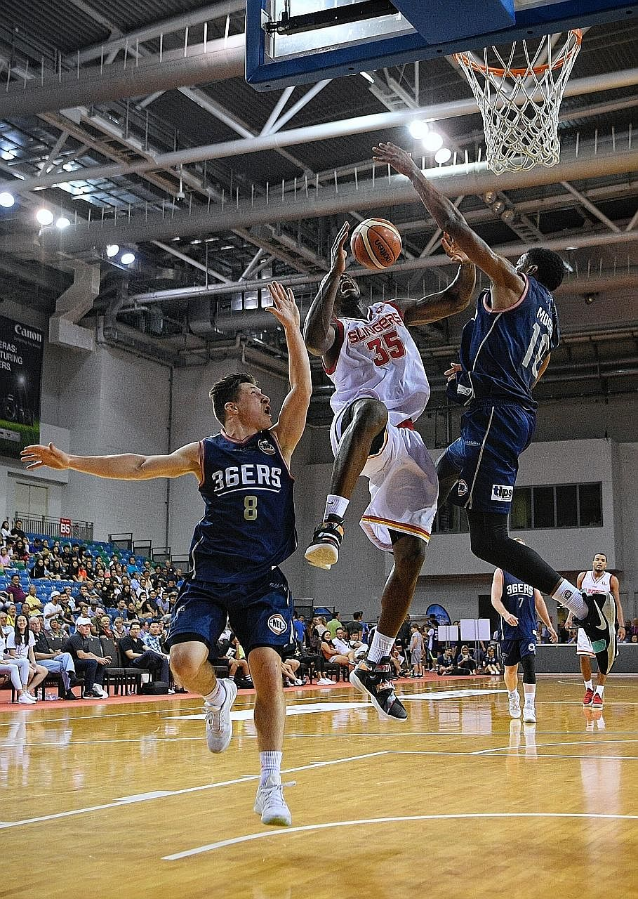 Ryan Wright of the Singapore Slingers going for a shot, as Nelson Larkins (left) and Ramone Moore of the Adelaide 36ers try to block him. The Australian team ran out easy winners 95-52 but the local side also qualified for the semi-finals.