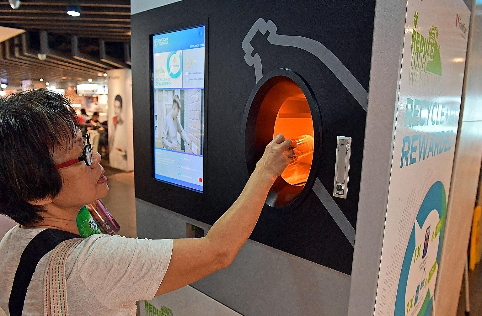 Madam Lau Hong Eng, 63, recycling drink cans at the reverse vending machine at Foodfare@Admiralty, which gives out money or coupons in exchange for an empty can or plastic bottle. Distributor Incon Green Singapore has plans to install 500 machines ac