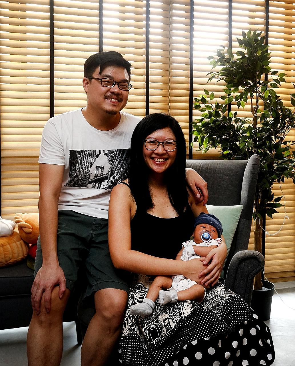 Upcycled wine crates are used as shelves in the living room, especially for the toy collections of home owners Marcus Wong and Gayle Tan (above, with their son, Logan Finn).