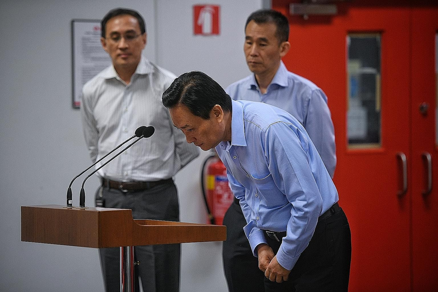 SMRT chairman Seah Moon Ming, flanked by Mr Desmond Kuek (left) and Mr Lee Ling Wee, bowing in apology during the media briefing on Oct 16.