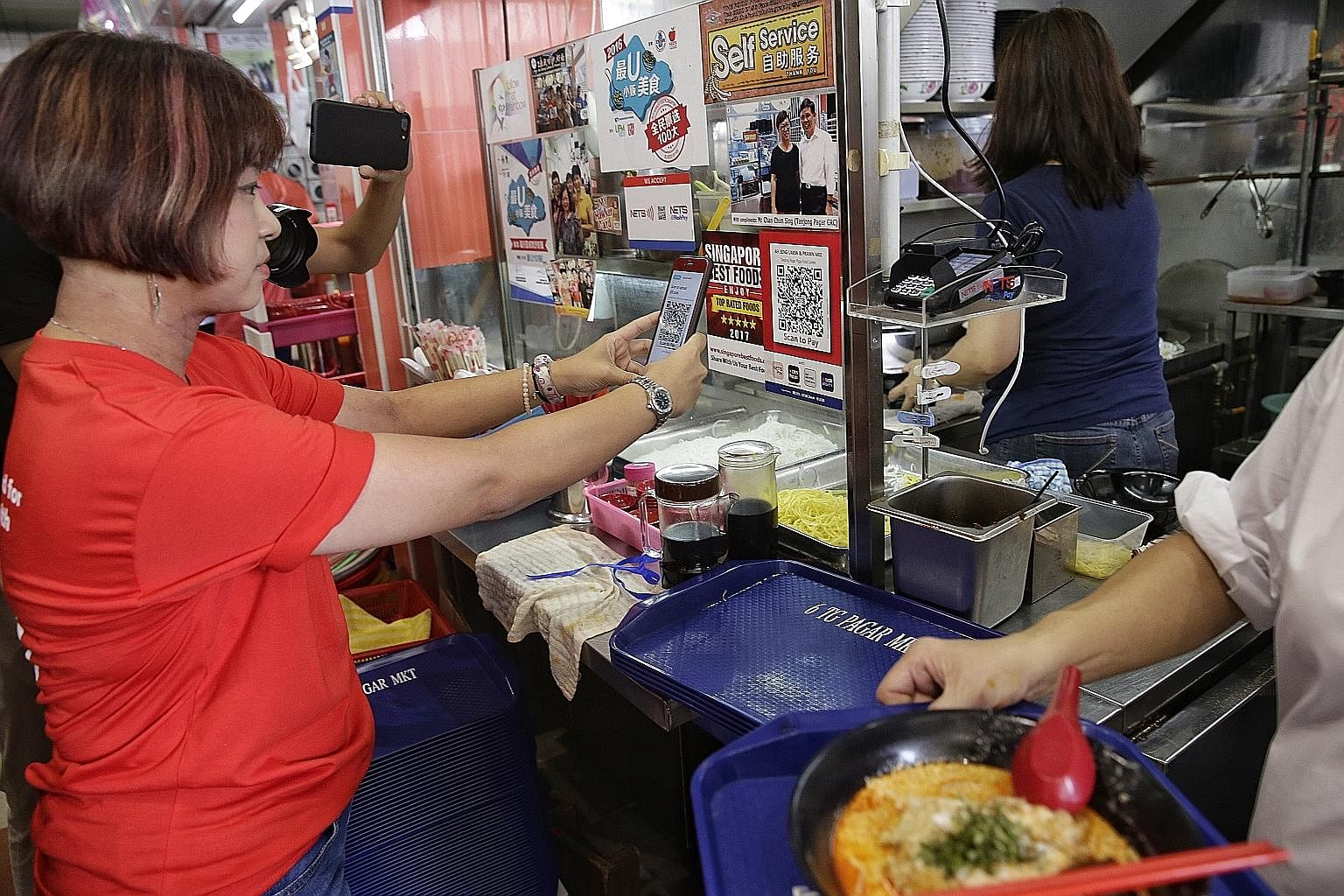 A customer scanning a QR code to pay for her meal at Tanjong Pagar Plaza Market and Food Centre. The tie-up between Nets and the hawker centre allows cashless payments at close to 50 stalls.