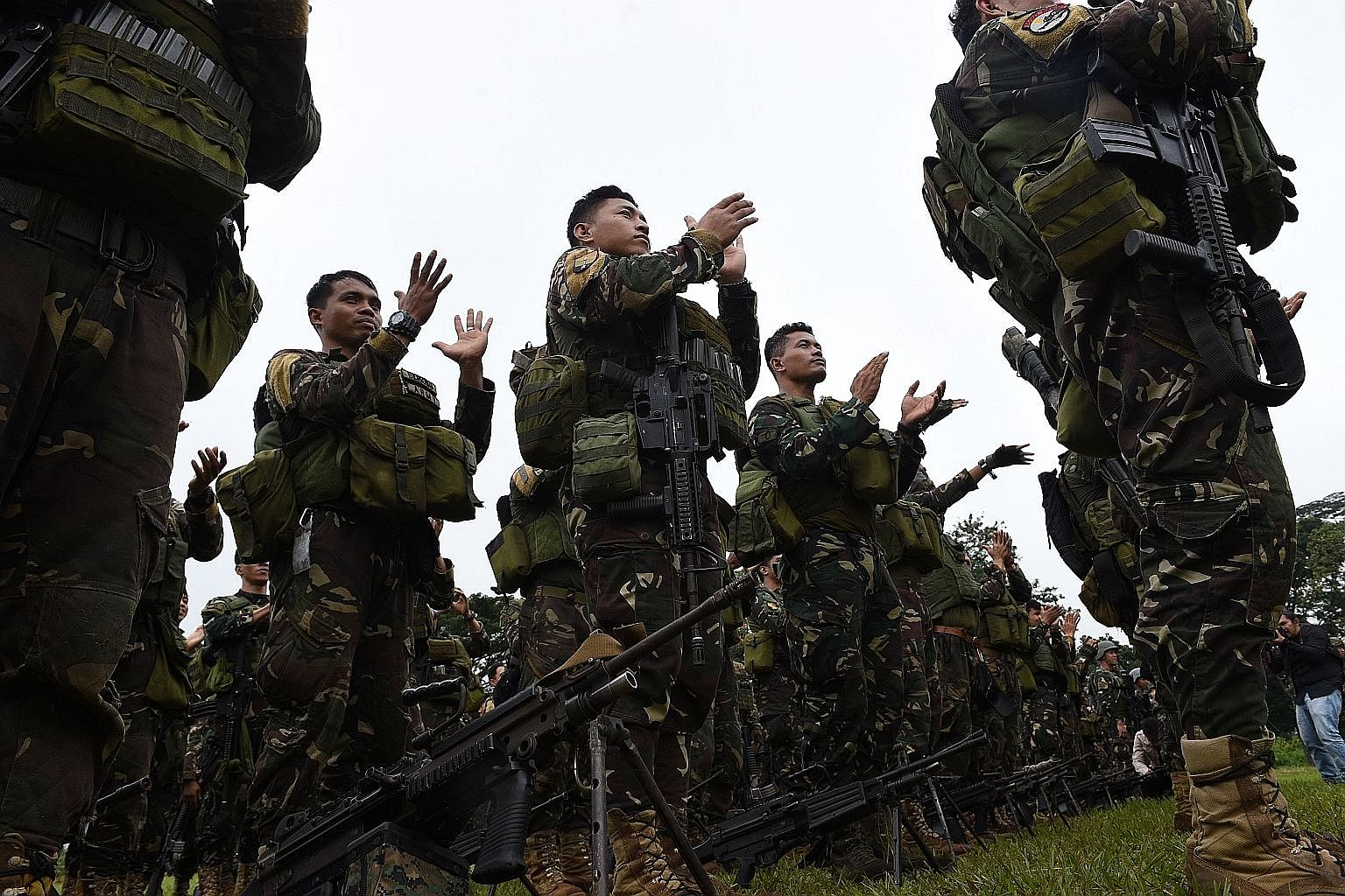 Philippine soldiers who fought against ISIS-affiliated militants applaud during their send-off ceremony inside a military camp in Marawi on the southern island of Mindanao yesterday. While the months-long siege of Marawi has effectively ended, the wa
