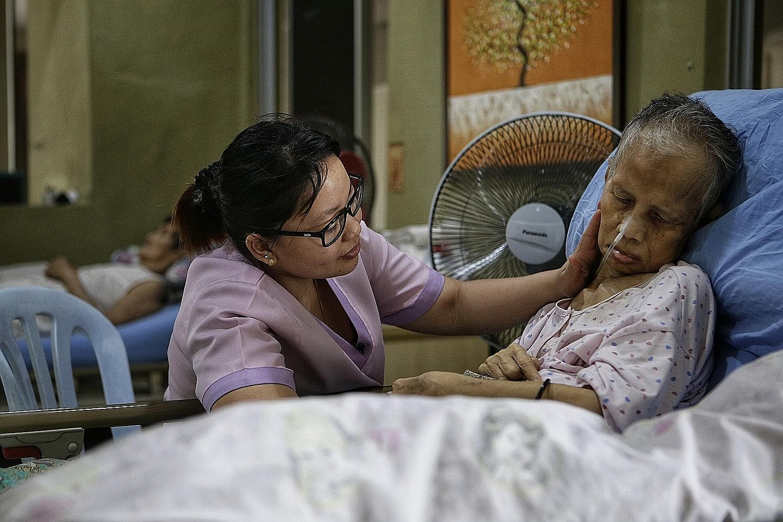 Senior nurse Liew Seenah, 30, consoling 69-year-old Madam Pungut Jumadi at Green Acres Nursing Home (below) in Johor Baru, about 20 minutes' drive from the Causeway. The owner of the home, Mr Yeo Kok Leong, is hoping to find Madam Pungut's family in