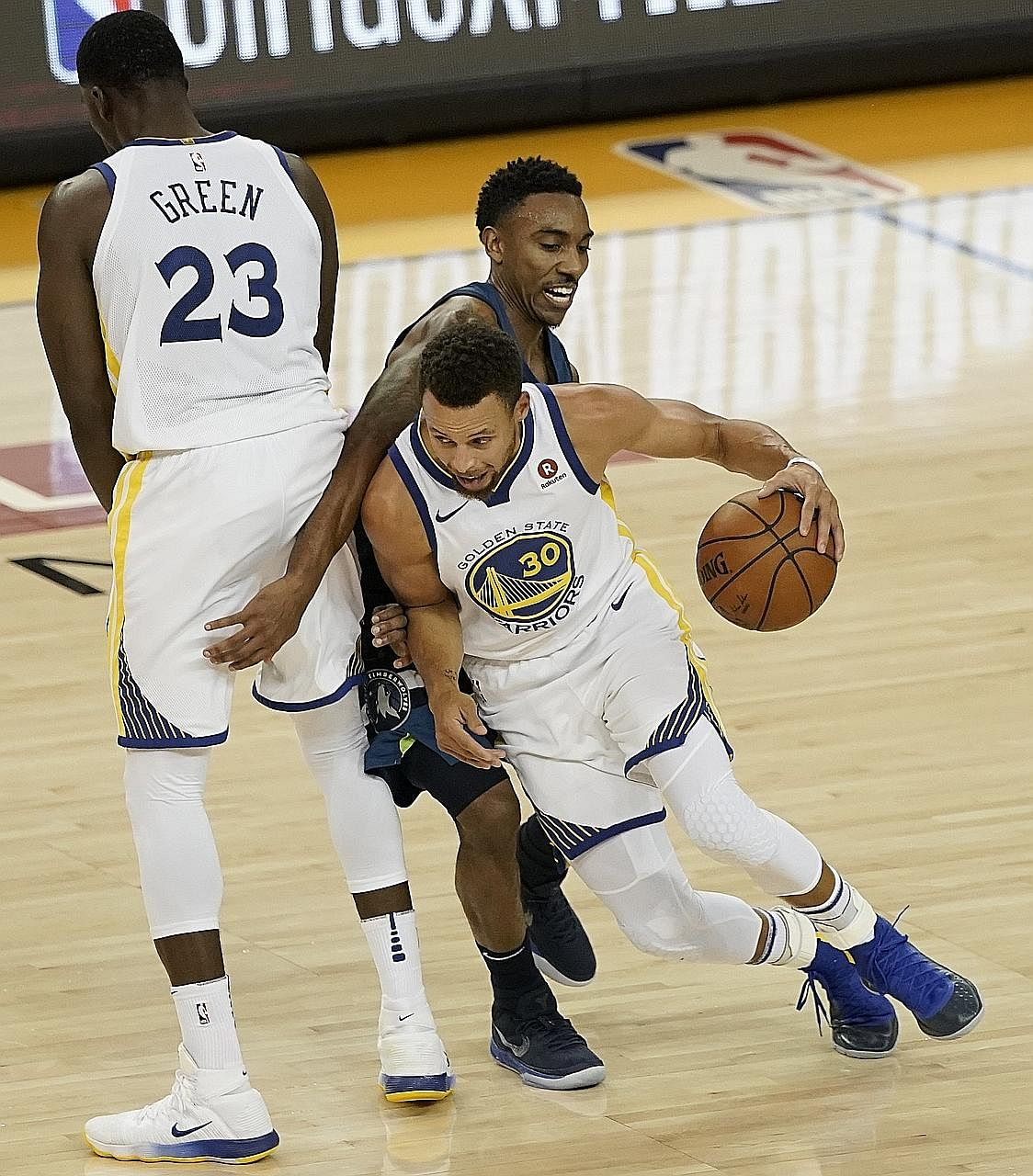 Golden State Warriors' Stephen Curry and team-mate Draymond Green executing a pick and roll to evade the defence of Minnesota Timberwolves guard Jeff Teague during their NBA game on Wednesday. Golden State won 125-101.