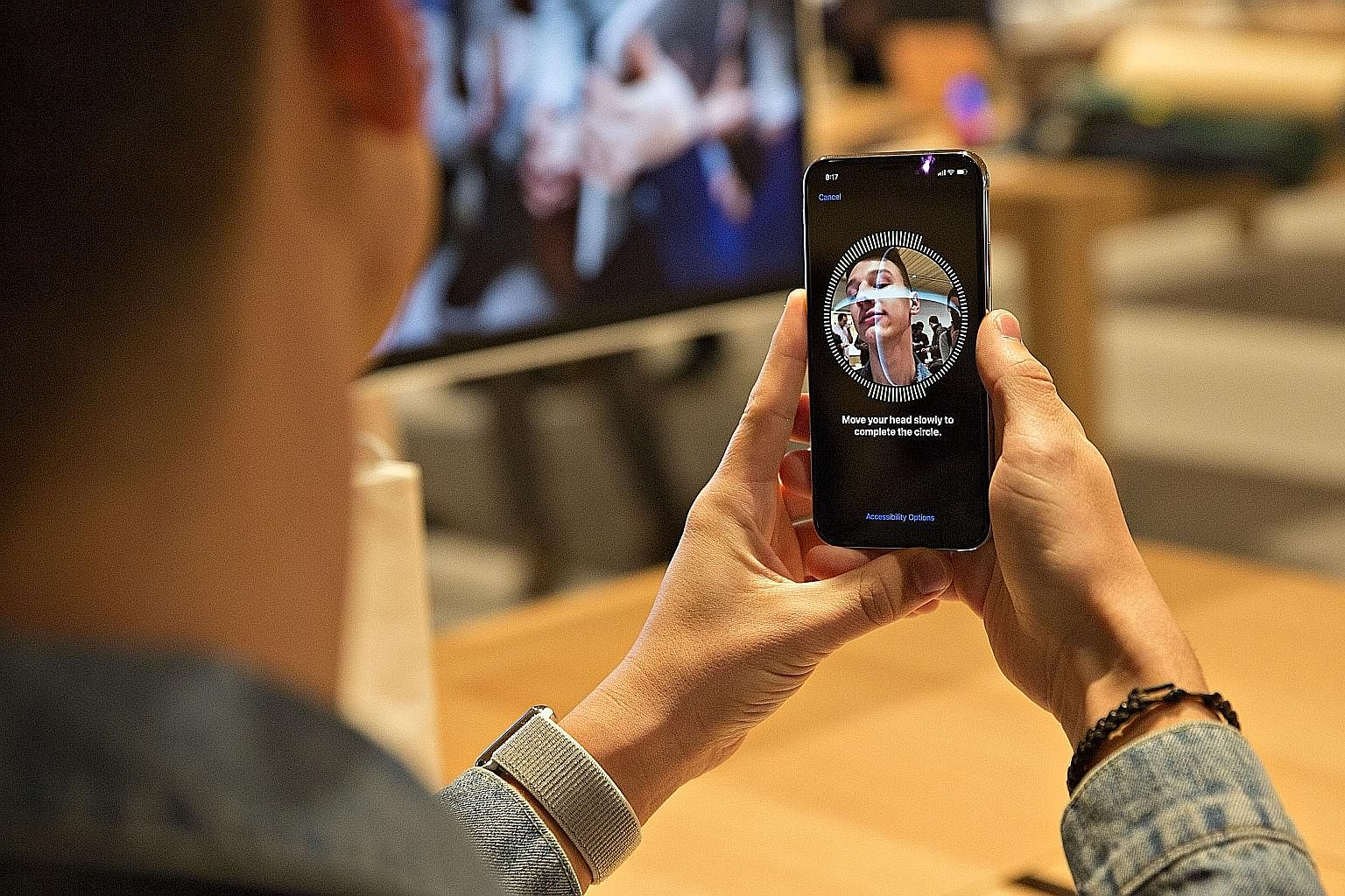 An iPhone X user setting up Face ID on his phone. The phone uses infrared and 3D sensors to make a comprehensive map of a user's face. It is smart enough to detect changes to a face, such as with spectacles or a new beard, but cannot tell identical t