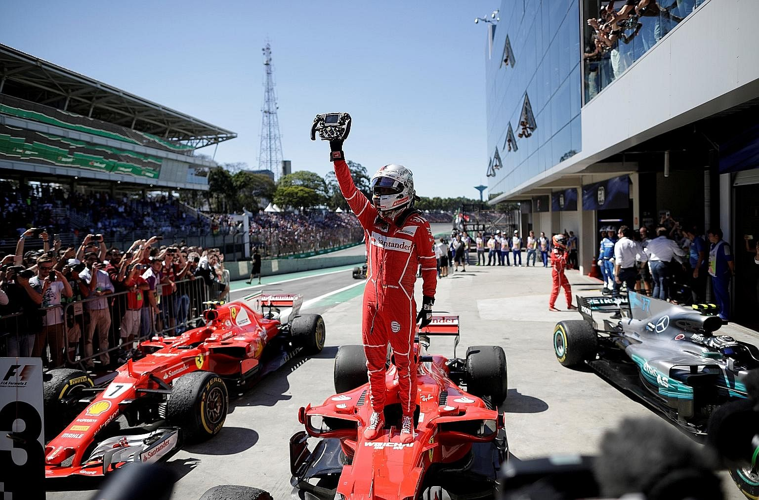 Sebastian Vettel of Ferrari holding up his steering wheel in triumph after winning the Brazilian Grand Prix on Sunday, his fifth win this season. Threats made by Ferrari chairman Sergio Marchionne to leave the sport were the talk of the paddock in Br