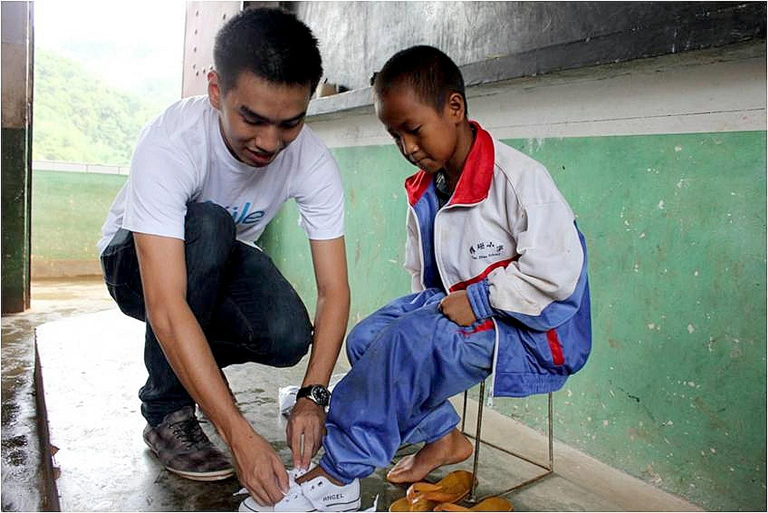 Mr Lee putting on shoes for a schoolboy in Lincang, Yunnan, in 2010. Soule's first batch of flip-flops sold out, and the proceeds were enough to buy 317 pairs of shoes for one entire school in Lincang. Mr Justine Lee was a rebellious child who did ba