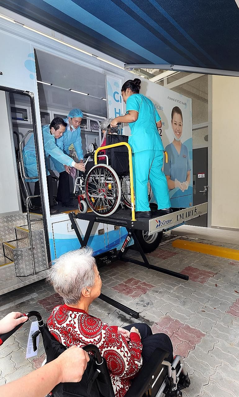 Staff at NTUC Health Nursing Home in Chai Chee helping residents to go for dental care appointments at a mobile clinic run by Unity Denticare parked on the home's premises.