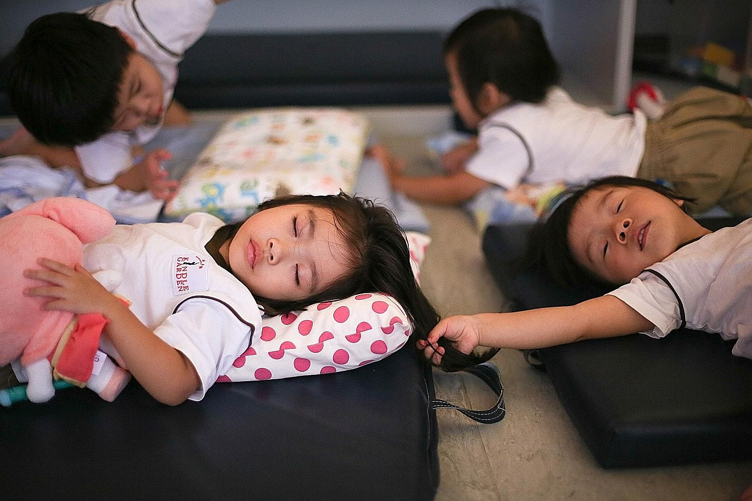 Nursery 1 classmates Oriana Yip (left) and Rhea Lim, both three, take a well-deserved nap after a day of activities and running around. To encourage independence, all the children lay out and put away their beds and sheets themselves. Those who strug
