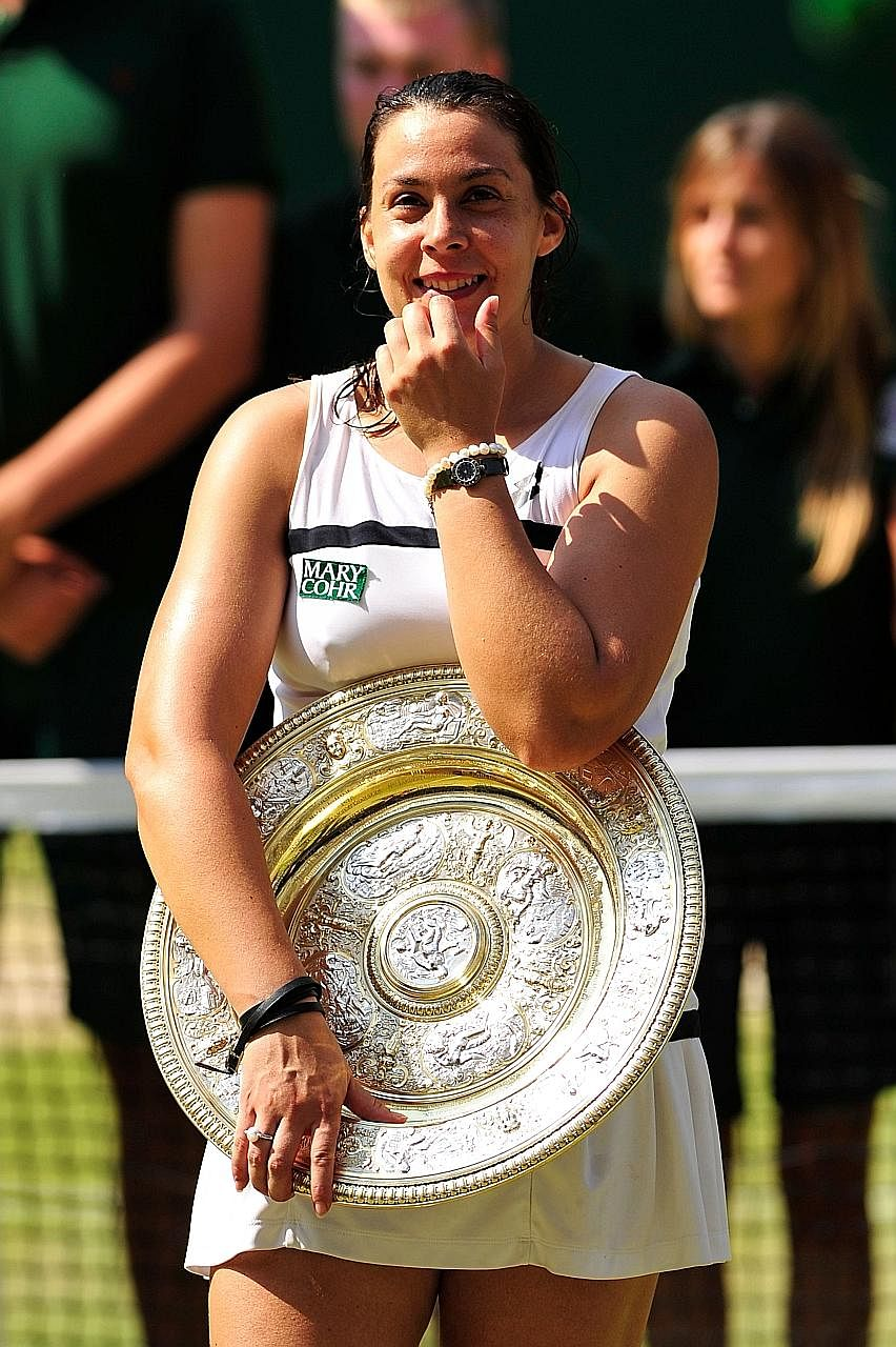 Marion Bartoli with the Venus Rosewater Dish after winning Wimbledon in 2013.