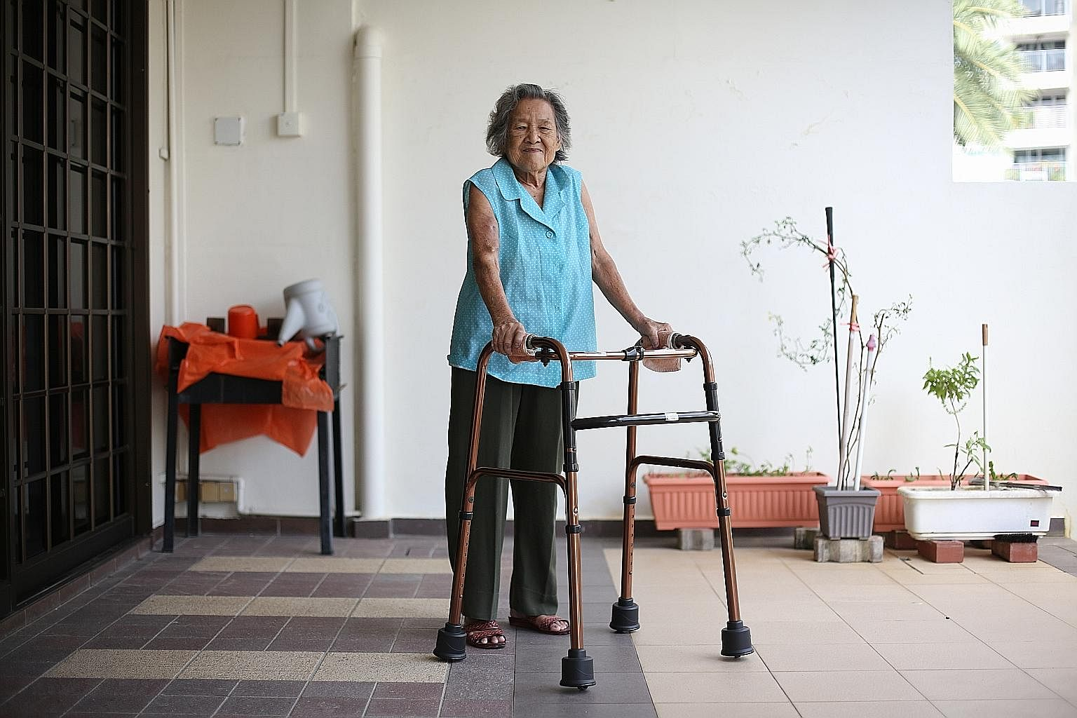 Madam Leck Peow Joo, who suffers from arthritis and end-stage kidney failure, uses the GlydeSafe frame to move around her home. Its retractable wheels allow her to push the frame instead of having to lift it with each step.