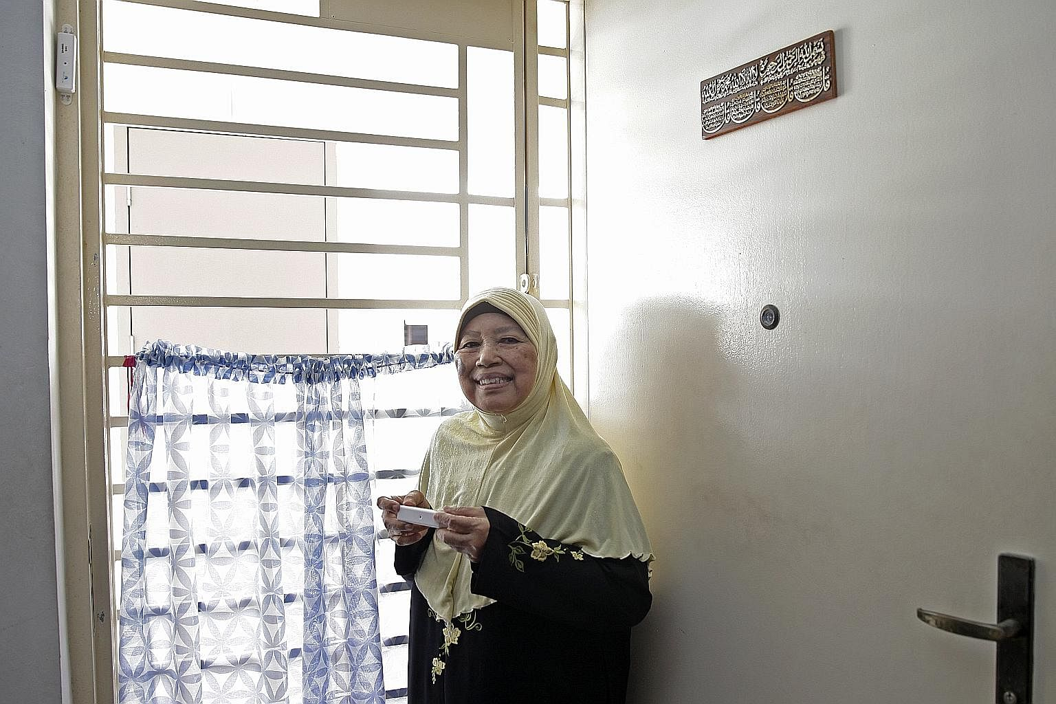 Madam Sitee Marnoor with a door sensor. A similar one was mounted on the frame of her main door in September. Since then, it has sent out three alerts.
