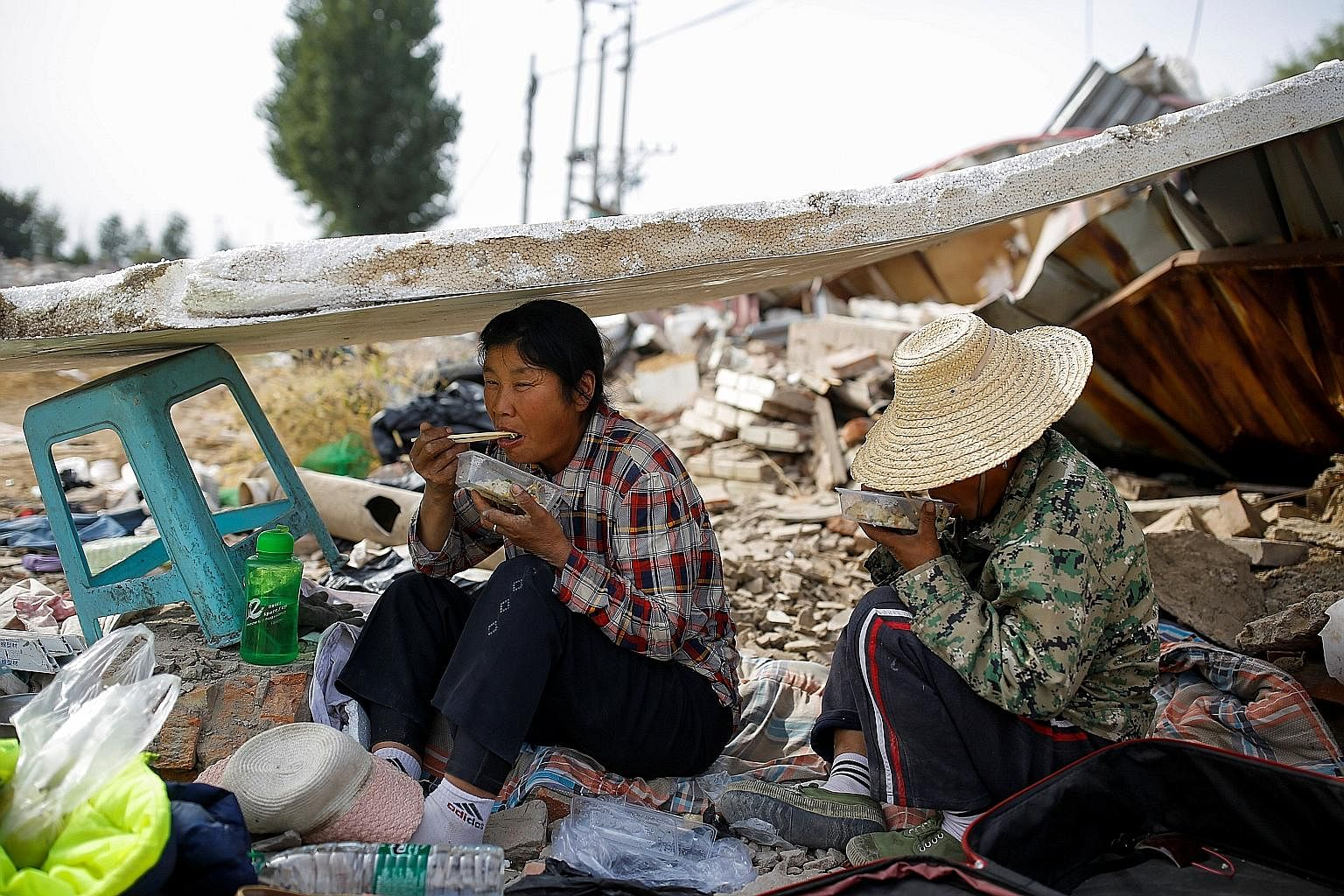 Migrant workers on their lunch break while collecting scrap materials on the outskirts of Beijing last October. More than 43 million people in China live on less than 2,300 yuan (S$470) a year, the poverty line set by the government, and roughly 40 p