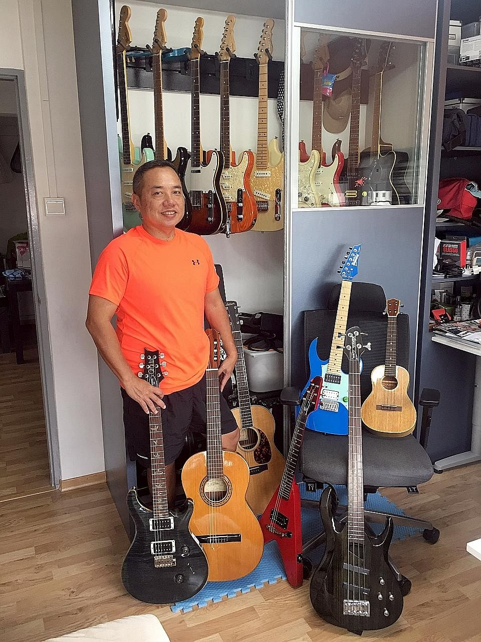 Mr Sim Hong Huat with his collection of 20 stringed instruments, mainly guitars (above), and playing at Eusoff Hall during his university days (left).