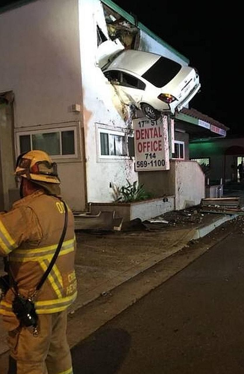 The Nissan sedan hanging from the second storey of the dental office building in Santa Ana, California, on Sunday. Police said the car went airborne after clipping a median. Both the driver and passenger suffered injuries.