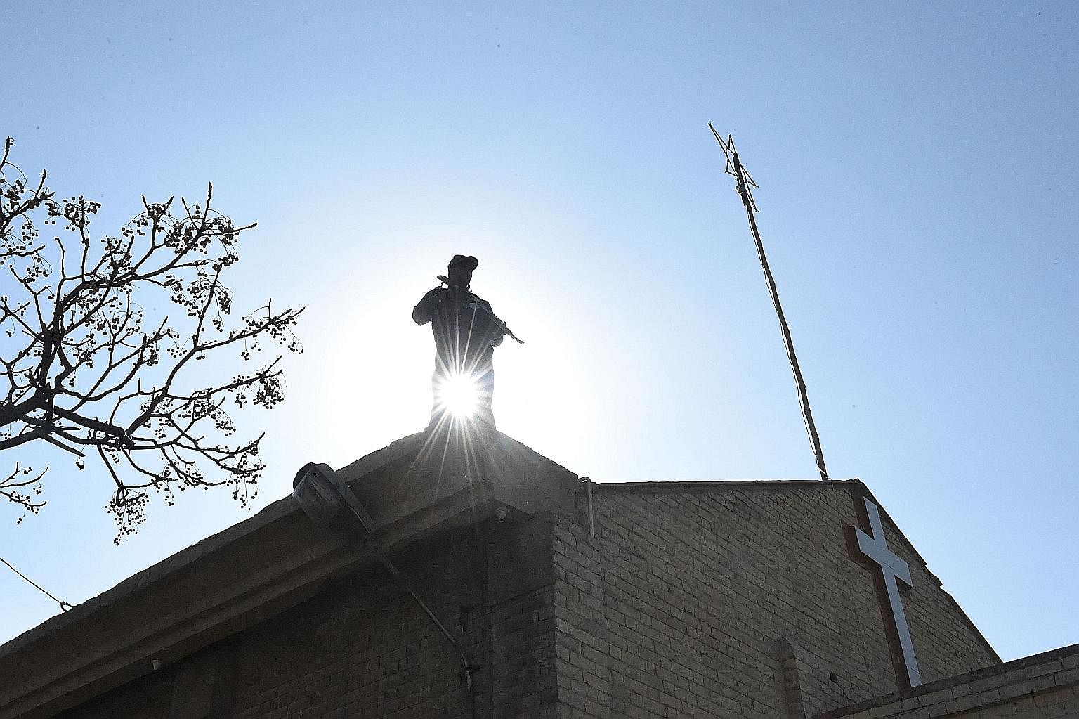 A policeman standing guard on the roof of a Methodist church in Quetta last December, a day after it was attacked by the ISIS group.