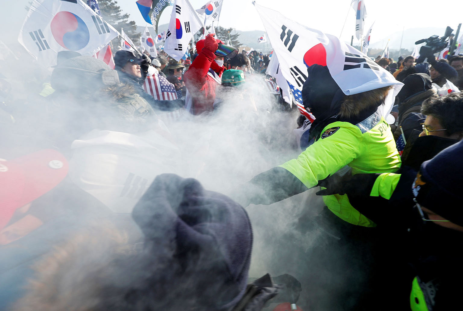 "Police (in green) try to stop demonstrators during an anti-North Korea protest in Pyeongchang yesterday. Seoul is hoping this Winter Olympics will be a ""Peace Olympics"", though Washington and other parties are concerned that the games may be exploite"
