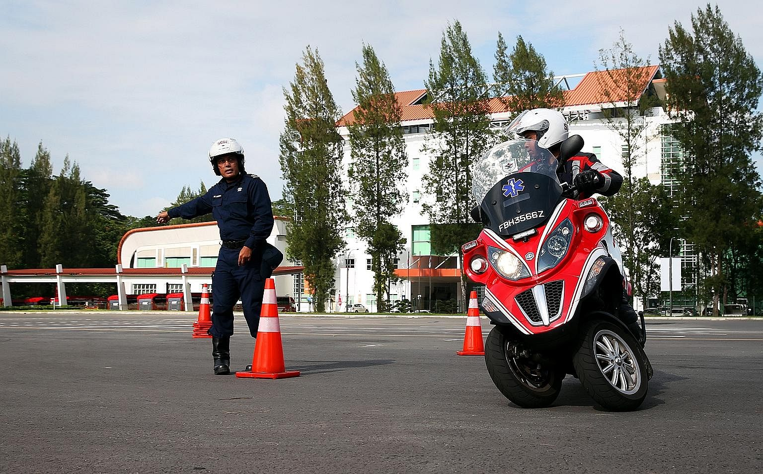 When a turnout occurs, firebiker Md Hilmi Md Fuad slides down a pole (left) to get to his three-wheeled scooter quickly. At the Civil Defence Academy in Jalan Bahar, firebikers like Staff Sergeant Hilmi are required to go through a riding course to b