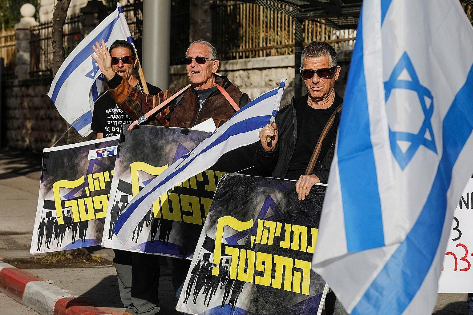 """Protesters holding signs saying """"Netanyahu resign"""" at a demonstration in front of Mr Benjamin Netanyahu's residence in Jerusalem on Wednesday."""
