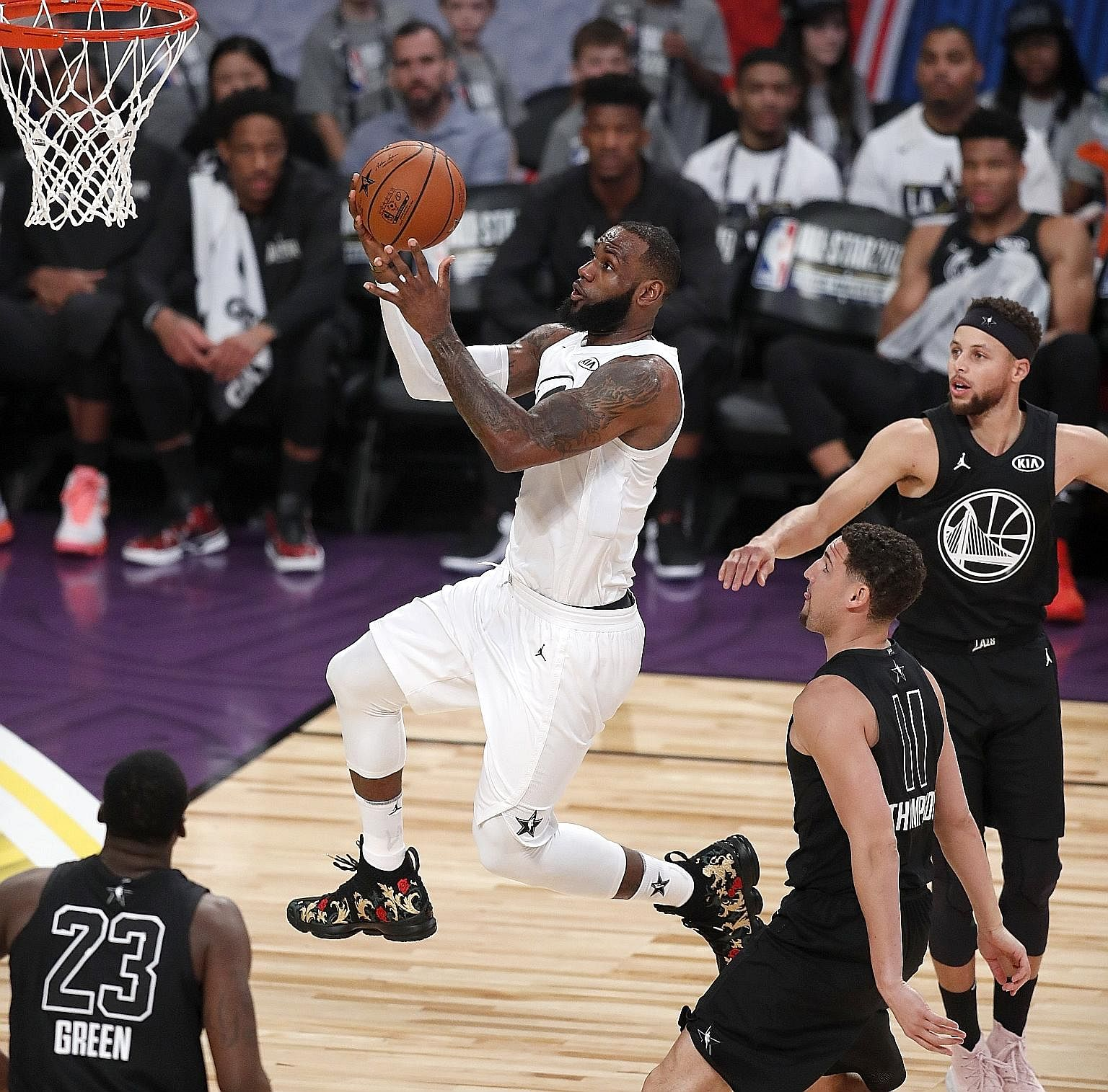 LeBron James going up for a shot after getting past (from left) Draymond Green, Klay Thompson and Stephen Curry in Sunday's All-Star Game.