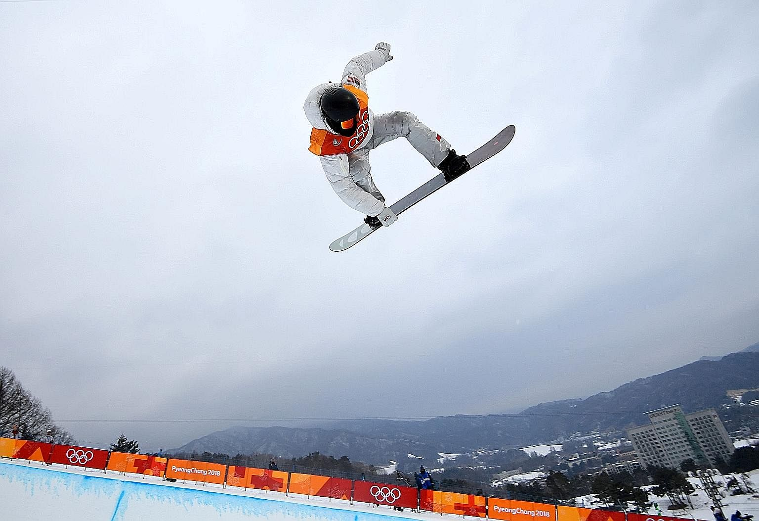 American Shaun White executing a move in the half-pipe final at Phoenix Snow Park on his way to a third Winter Olympics gold medal.