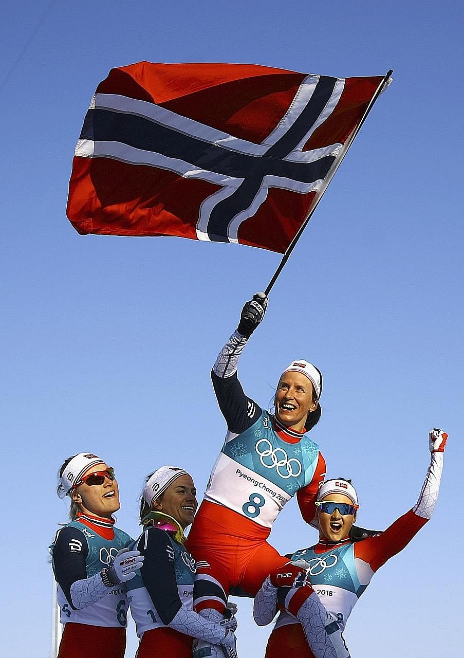Marit Bjoergen, winner of the 30km cross-country mass start race, being feted while waving the Norwegian flag. Her fifth medal in Pyeongchang took her tally to eight golds, four silvers and three bronzes over five Games - making