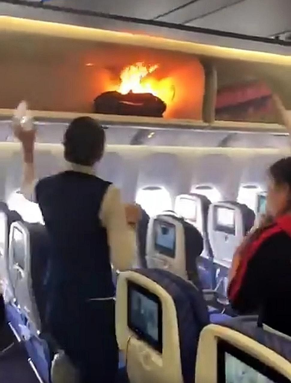 A flight attendant trying to douse the flames from a passenger's cabin bag. The incident on the China Southern Airlines plane took place as passengers were boarding in Guangzhou.