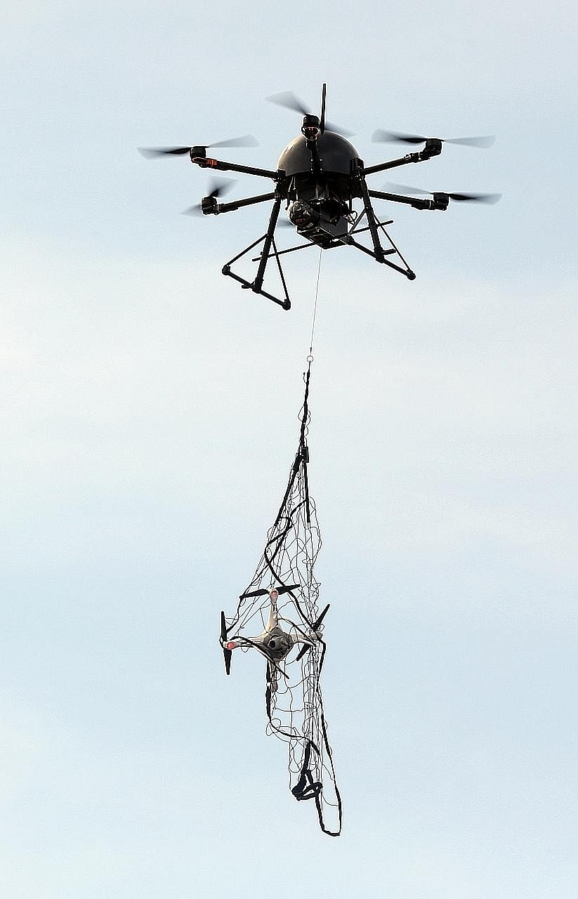"A ""drone-catcher"" homes in on an errant drone and catches it with a net. Counter-drone systems are among the features of smart airbases of the future."