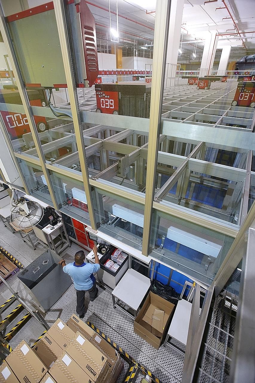 A worker at the FairPrice Hub distribution centre loading a bin with items for storage. The new automated storage and retrieval system brings bins containing order items to employees stationed at picking bays, where they bag and dispatch items for de