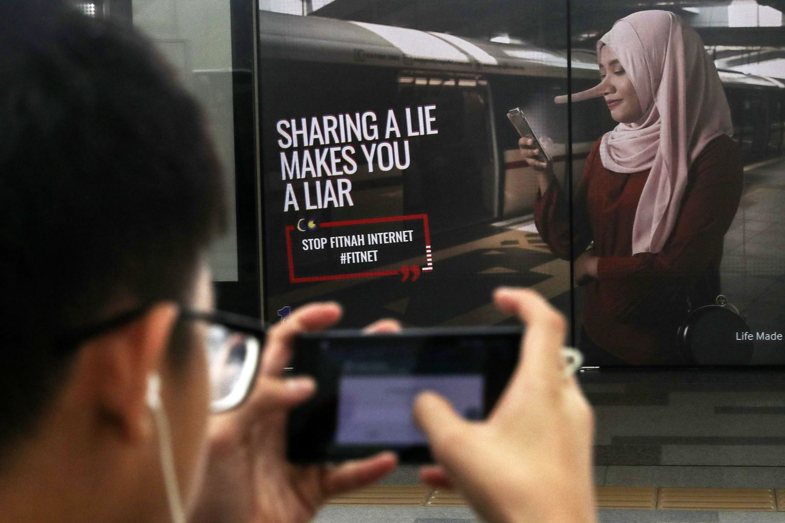 An advertisement warning members of the public not to spread fake news is seen in Kuala Lumpur on March 31, 2018. Malaysian lawmakers approved an anti-fake news law on April 2, 2018. Image: EPA-EFE