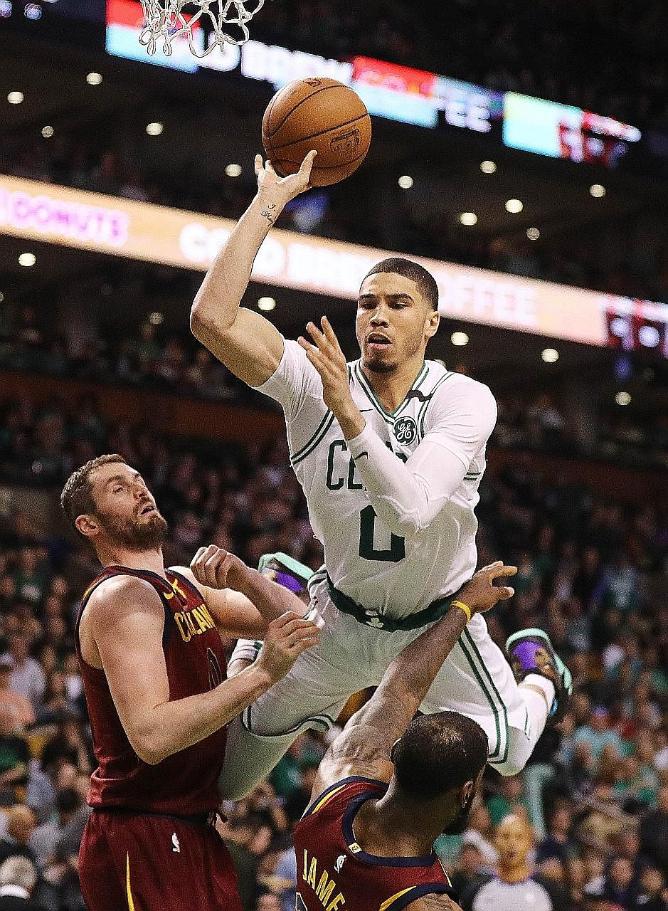 Boston's Jayson Tatum is airborne as he drives past Kevin Love and LeBron James in the 108-83 victory over Cleveland in Game 1 of the Eastern Conference Finals.