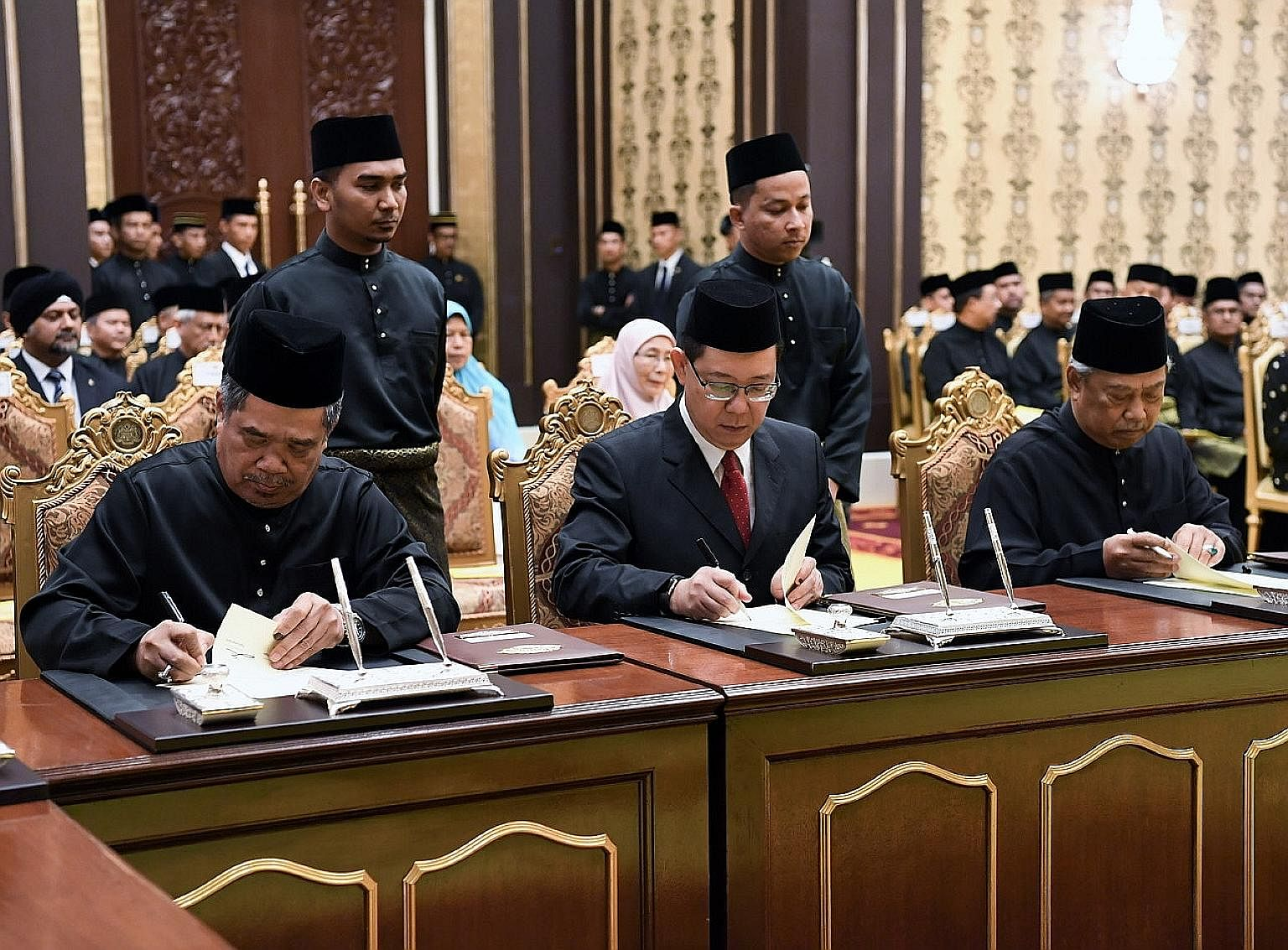 Defence Minister Mohamad Sabu, Finance Minister Lim Guan Eng and Home Minister Muhyiddin Yassin signing their appointment letters at the Istana Negara in Kuala Lumpur yesterday. They were among 13 members of Tun Dr Mahathir Mohamad's core