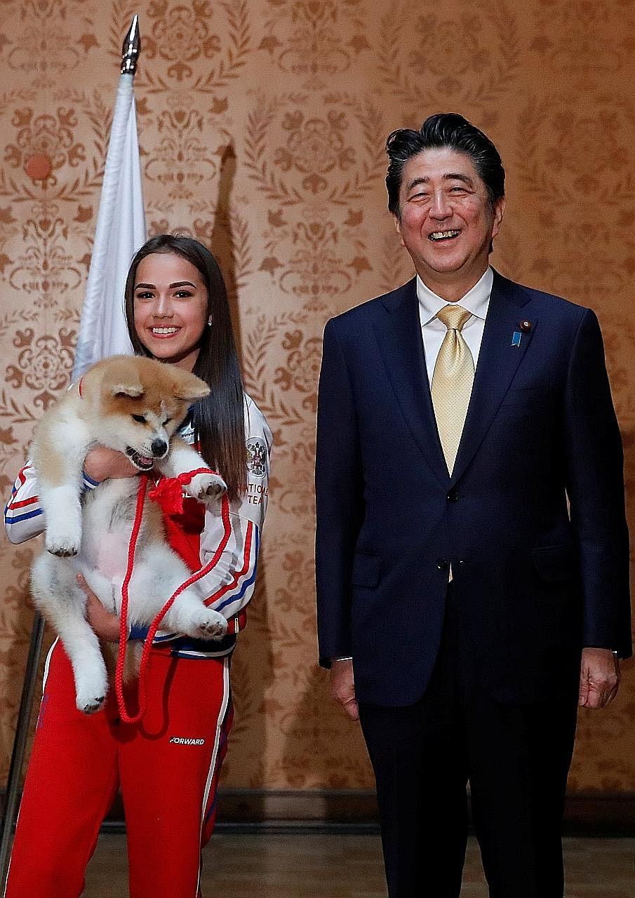 Russian figure skating gold medallist Alina Zagitova and Japanese Prime Minister Shinzo Abe with the puppy