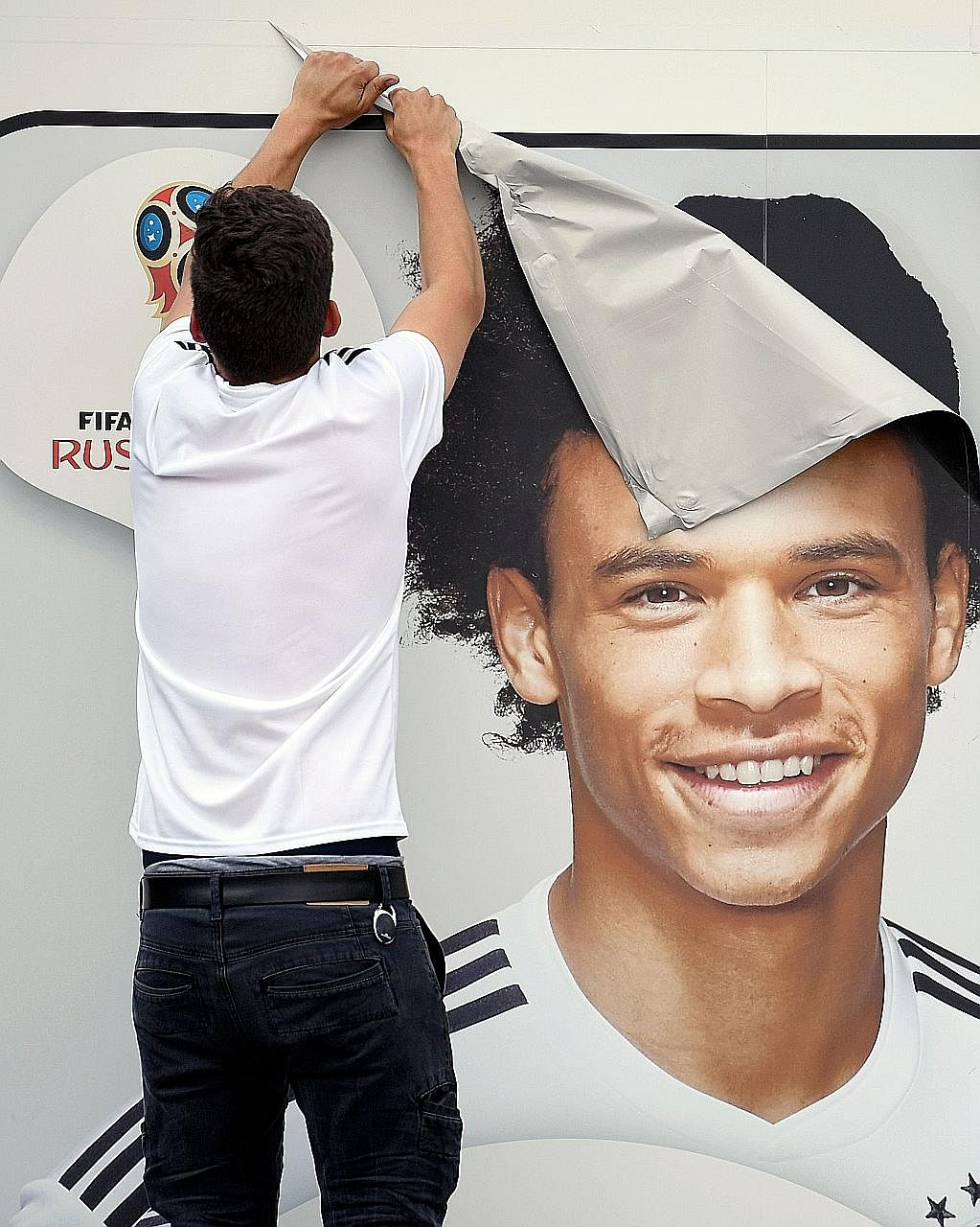 An employee removing a poster of Leroy Sane from the facade of the German Football Federation's museum in Dortmund yesterday. Coach Joachim Low dropped the Manchester City midfielder from his squad for the World Cup.