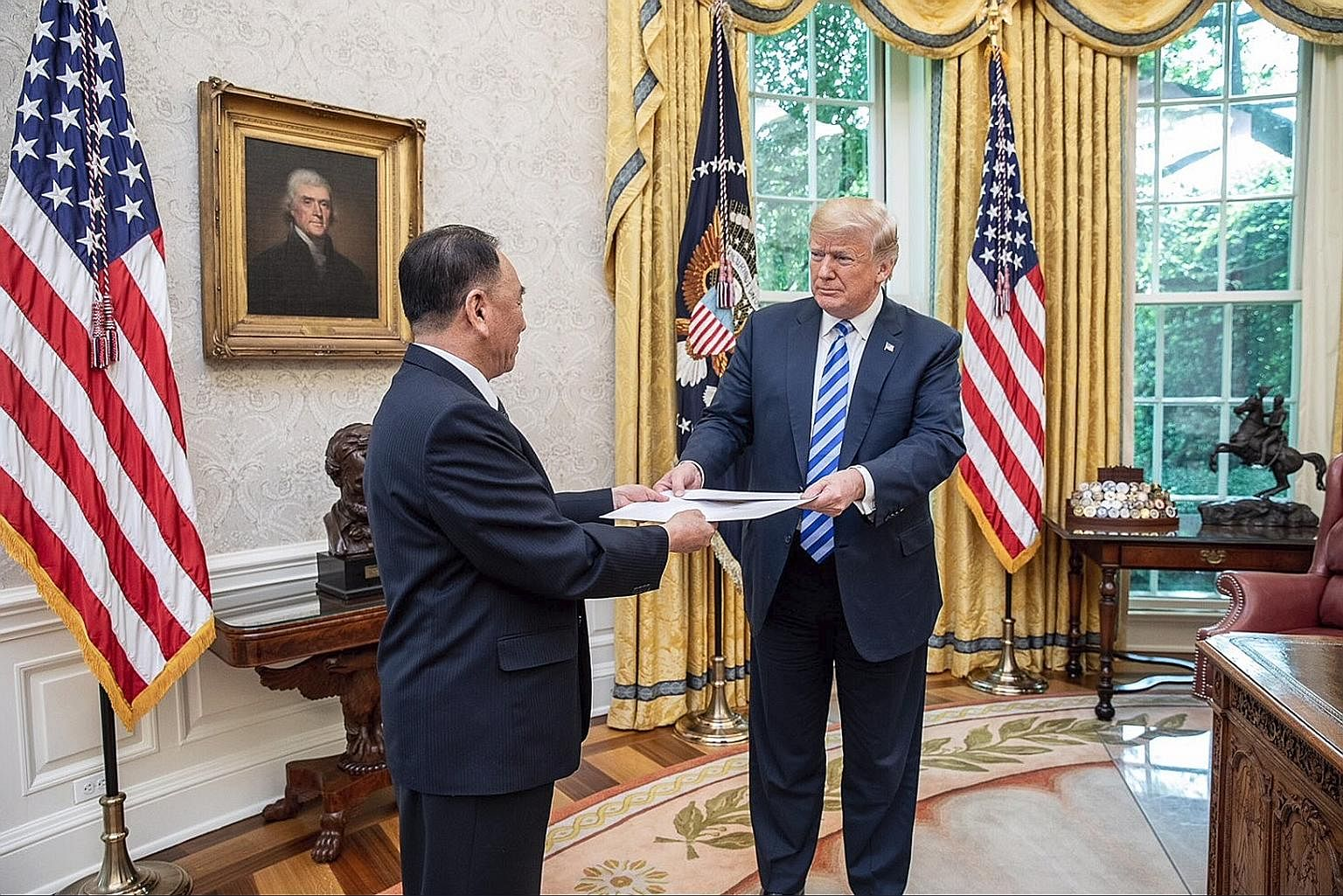 General Kim Yong Chol, vice-chairman of DPRK's Workers' Party of Korea central committee, handing a letter from North Korean leader Kim Jong Un to US President Donald Trump at the Oval Office at the White House in Washington on June 1.