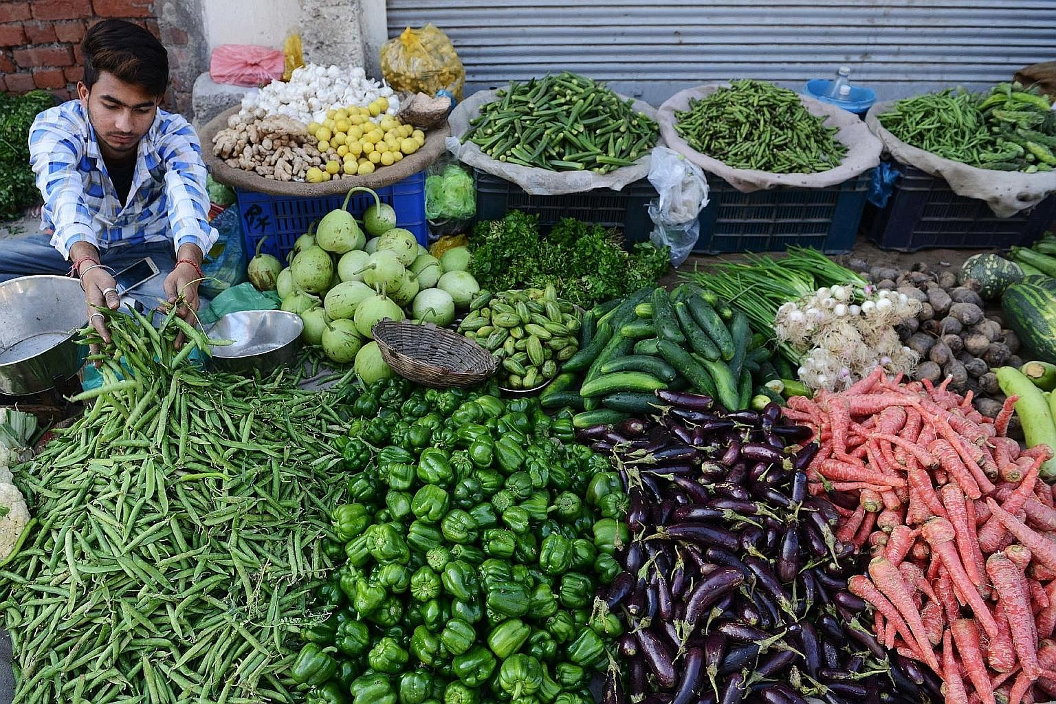 A vegetable seller in India. Global warming will likely make vegetables scarcer worldwide, said researchers.