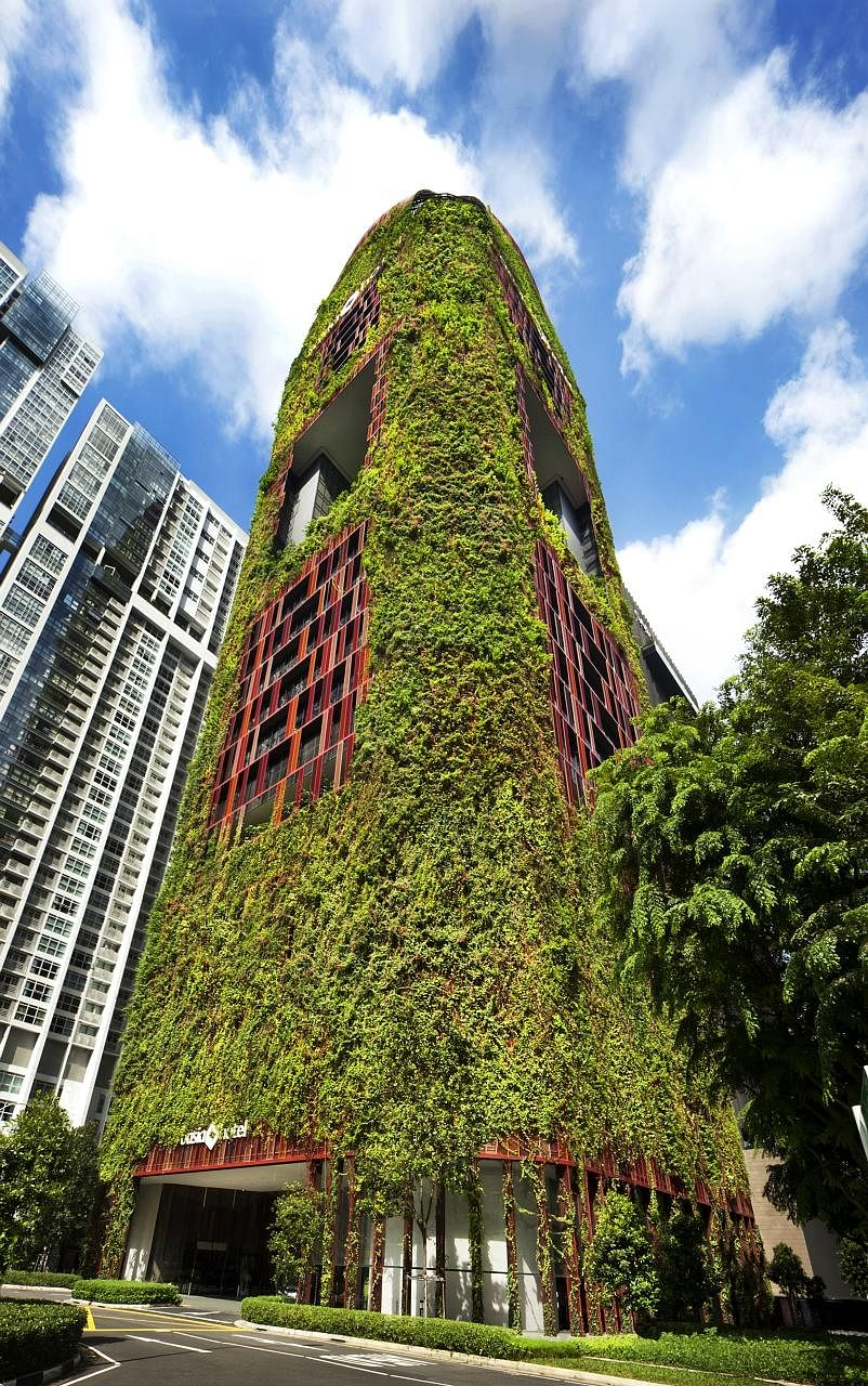 The 27-storey Oasia Hotel Downtown features a plant-covered facade of red and green and outdoor communal spaces along its height.