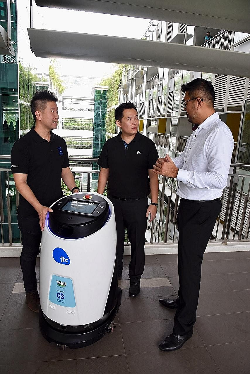 (From left) Gaussian Robotics director Aloysius Chong, JTC building management division director Jason Foo and WIS chief commercial officer Kelvin Lee with robot Scrub 50.