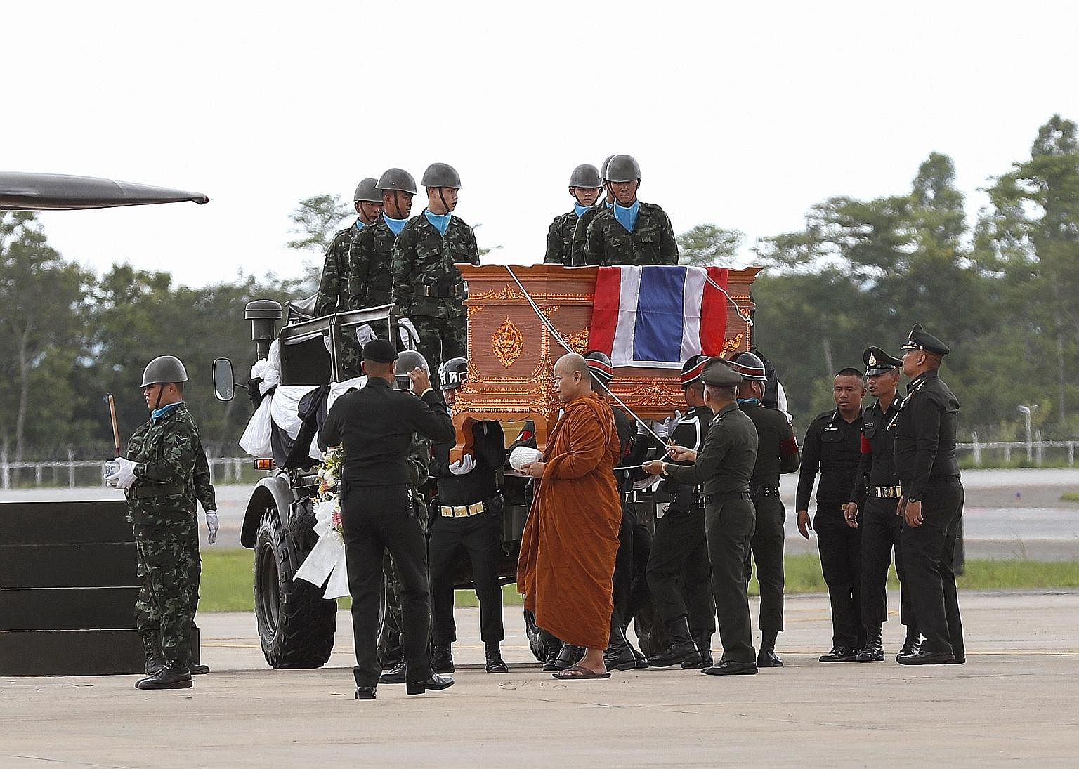 A Thai Buddhist monk leading a military honour guard carrying the coffin of former Thai navy Seal diver Saman Kunan (above) at Mae Fah Luang international airport in Chiang Rai yesterday.
