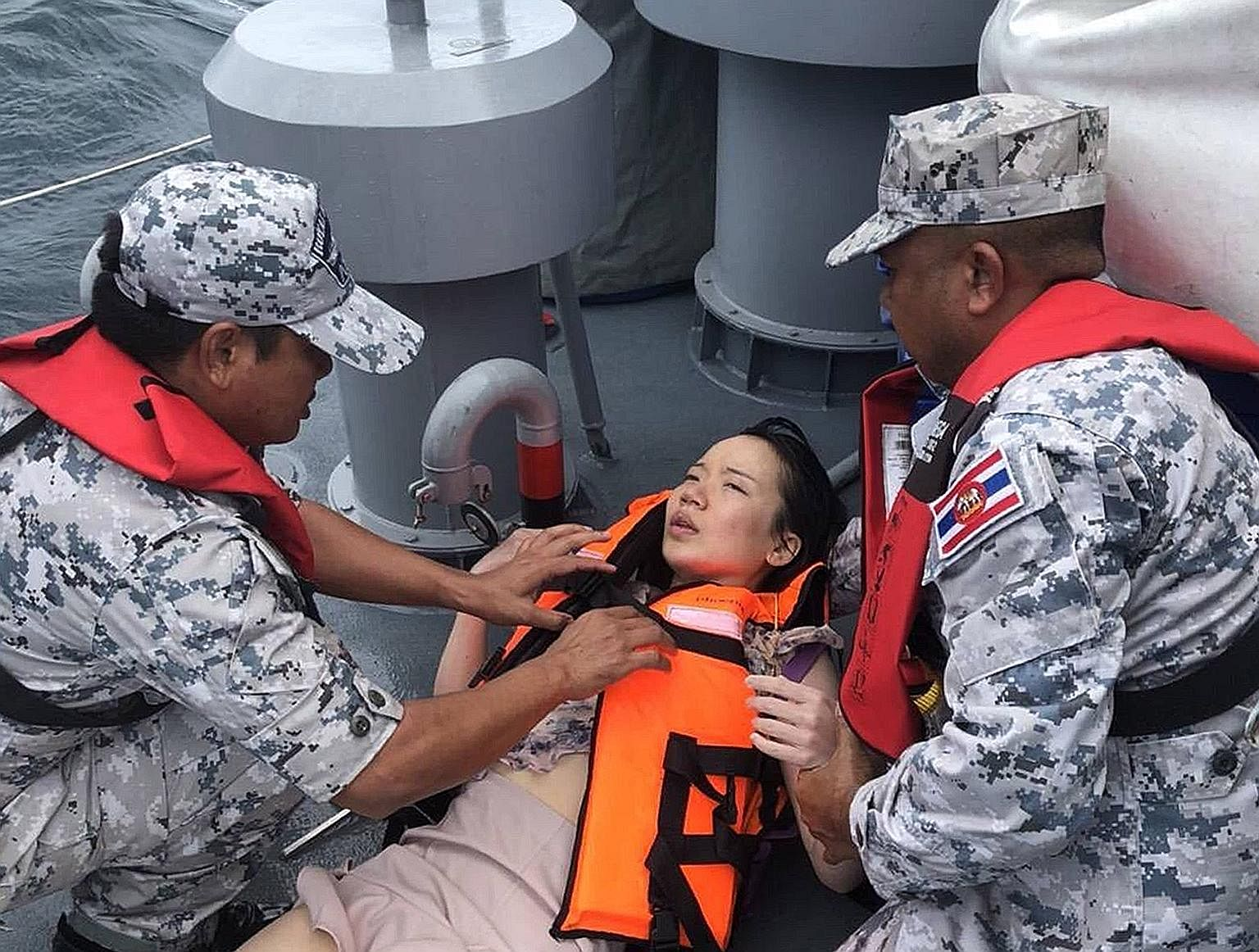 One day after bad weather and rough seas sank a boat carrying 105 people off the Thai resort island of Phuket, rescue workers began the grim task of collecting bodies instead of survivors such as this woman from the water. Thirty-three bodies were pu