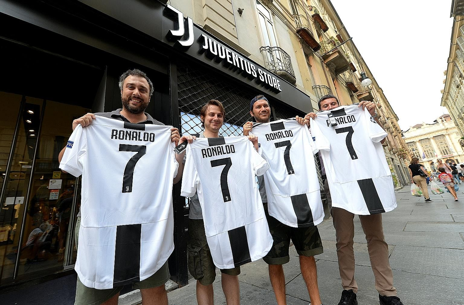 Juventus supporters posing with club shirts that have been adorned with the name and number of Cristiano Ronaldo after his €100 million (S$160 million) transfer from Real Madrid to the Italian champions on Tuesday.