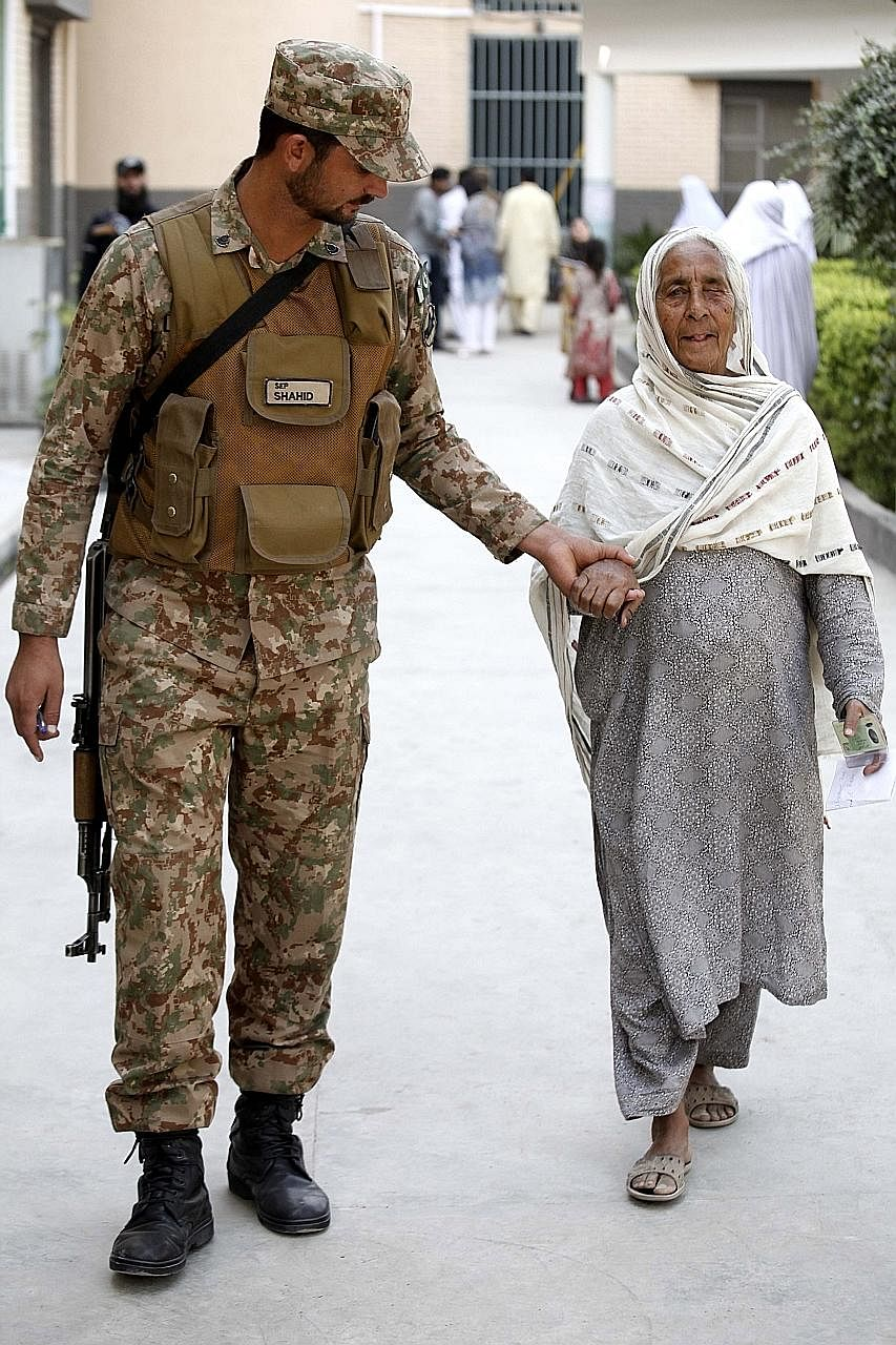 An Army soldier helping a woman as she