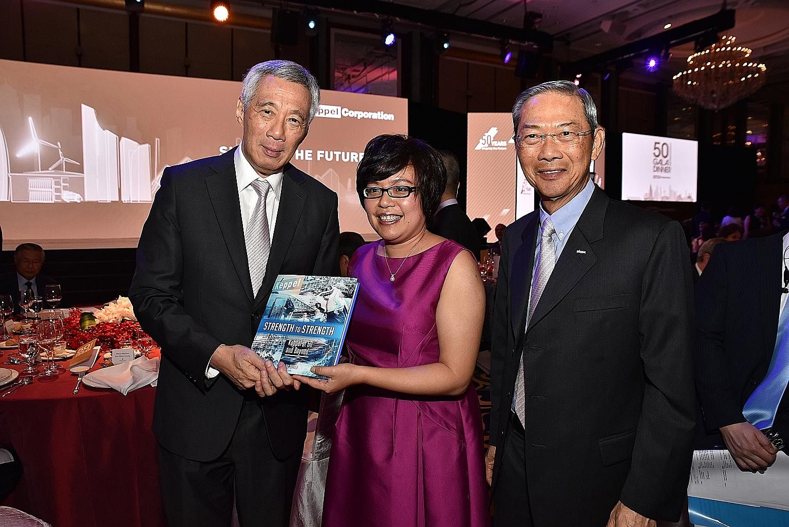 ST business editor Lee Su Shyan, who wrote a book charting Keppel's growth, with PM Lee and Keppel chairman Dr Lee.