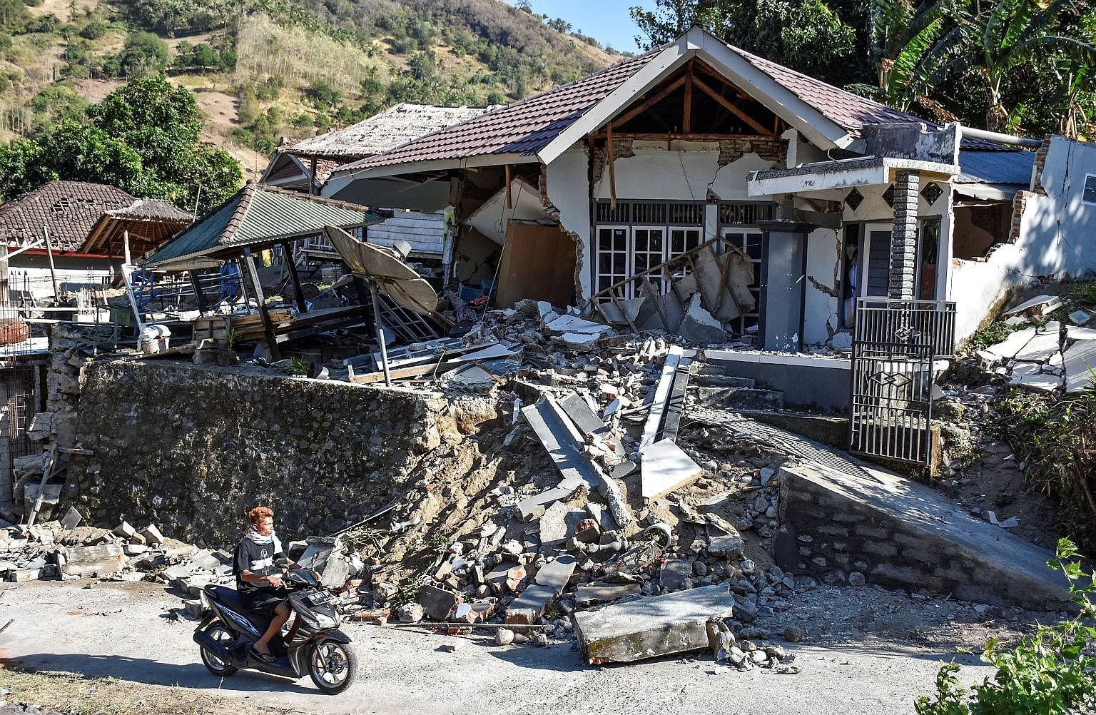 A damaged home in Pemenang, North Lombok, in Indonesia following Sunday's magnitude-7 earthquake. Indonesians on the resort island of Lombok began returning to their destroyed homes yesterday, after the powerful quake killed at least 98, including tw