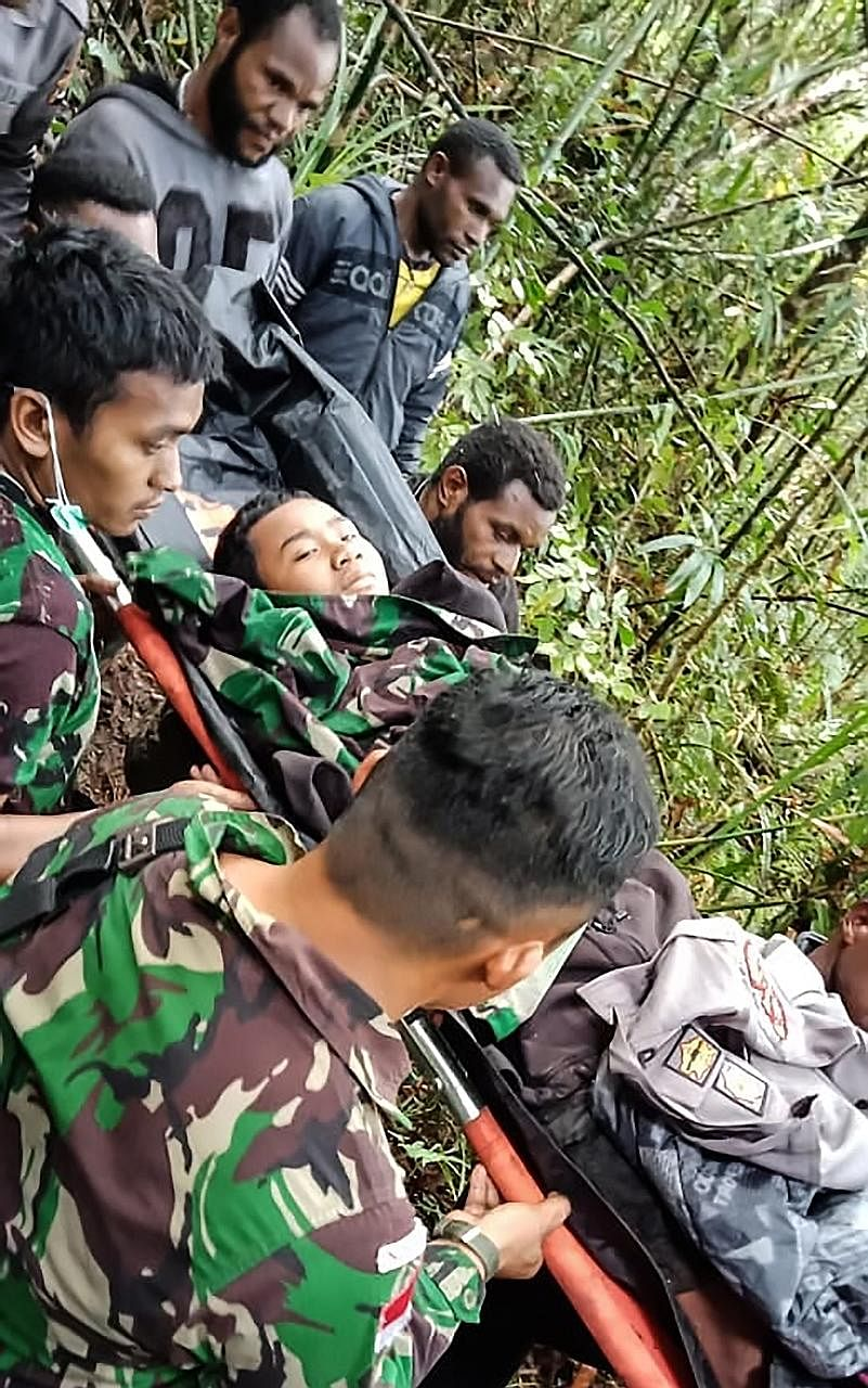 A rescue team evacuating the sole survivor of a plane crash from the crash site at Menuk mountain in the Oksibil sub-district of Papua, eastern Indonesia. The 12-year-old boy and eight other people were on board the Swiss-made Pilatus aircraft, which