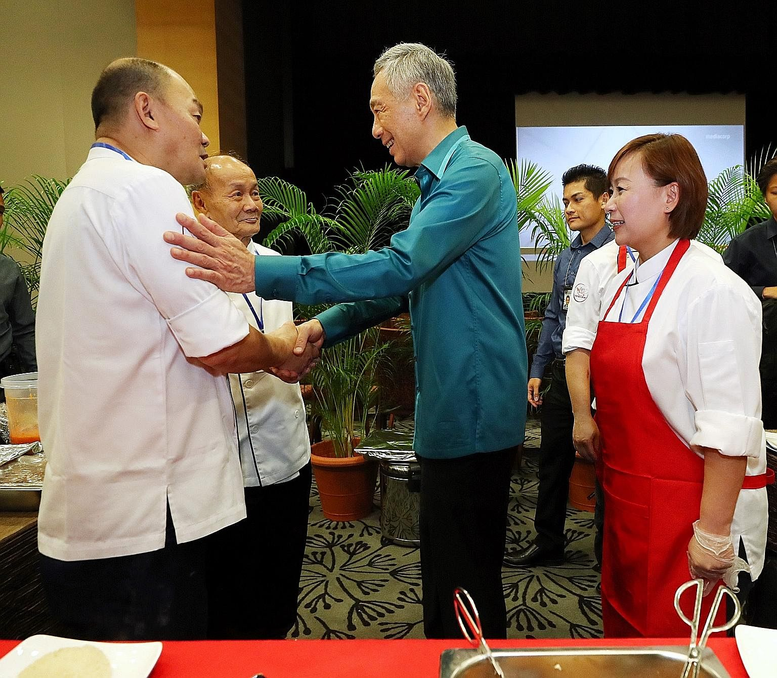 Prime Minister Lee Hsien Loong with Mr Raymond Kiang (far left), 57, who sells chicken rice at Our Tampines Hub, his father Kiang Joon Toh, 70, one of the pioneer chefs who developed Chatterbox chicken rice at Mandarin Hotel, and sister Susan. Singap