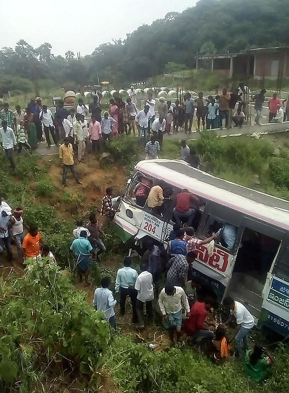 Rescuers trying to free people trapped in the bus that plunged into a valley in southern India yesterday.