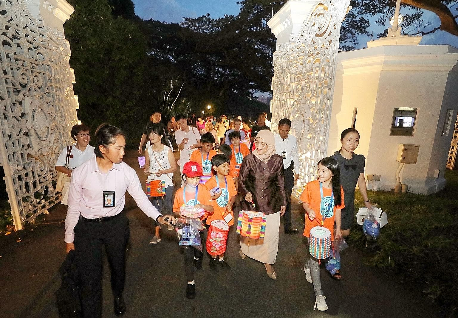 President Halimah Yacob leading children on a tour of the Istana grounds after a Mid-Autumn Festival picnic yesterday. The children were President's Challenge beneficiaries from Care Community Services Society, Focus on the Family, Daughters of Tomor
