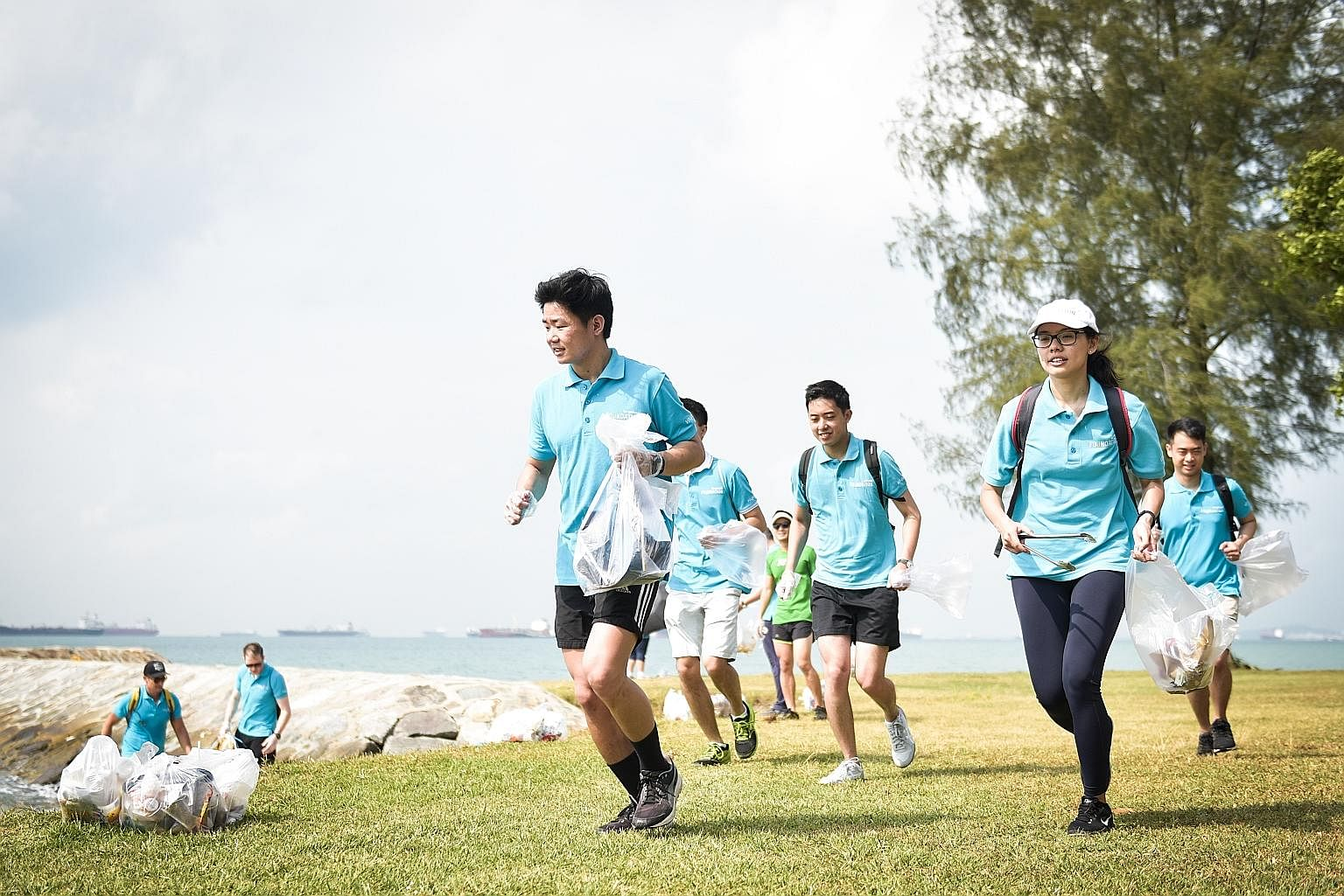 "Mr Lee Leong Hui (in front) plogging at the East Coast beach with his colleagues from property firm Lendlease last Thursday, as part of the company's annual community day. The term ""plogging"" is a mash-up of the word ""jogging"" and the Swedish words """
