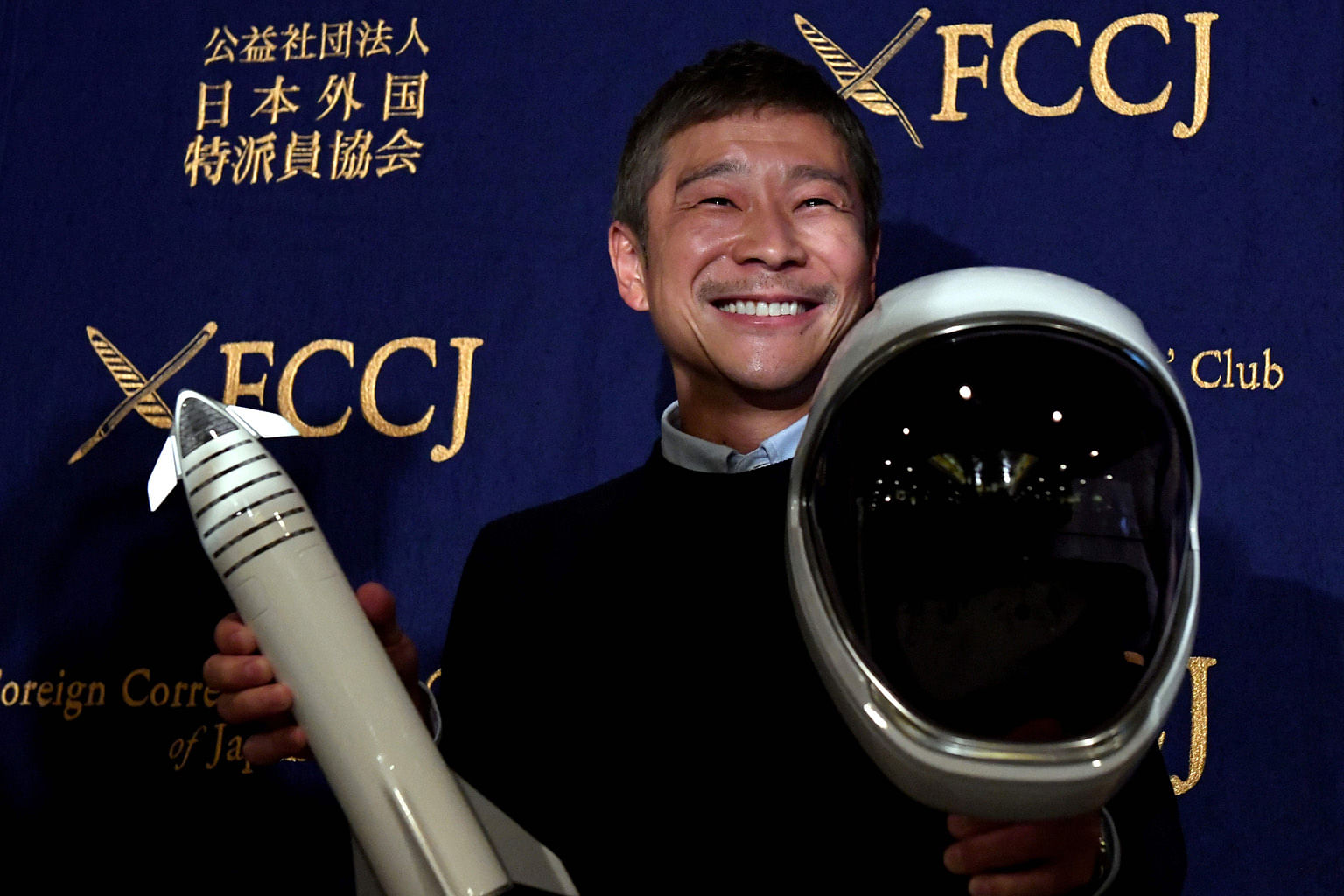 Mr Yusaku Maezawa with a miniature rocket and space helmet prior to the start of a press conference at the Foreign Correspondents' Club of Japan in Tokyo last Tuesday.